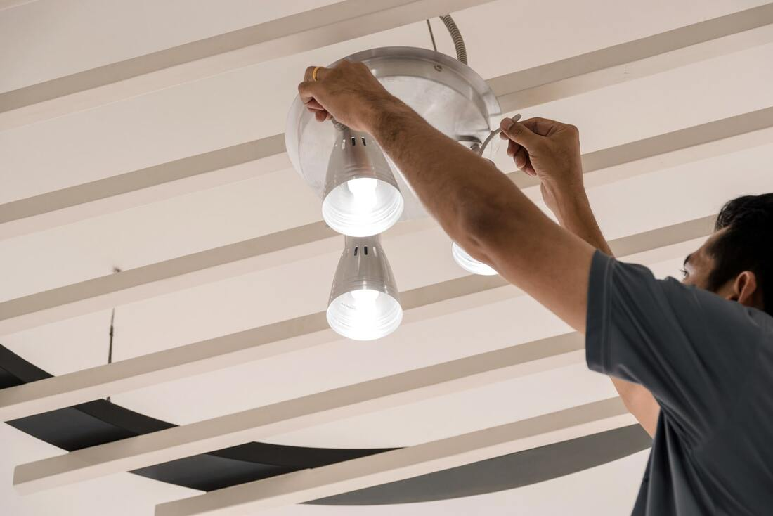 Electrician installing a three point ceiling light.